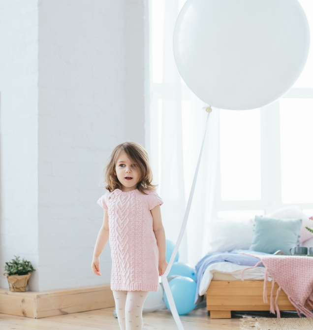 Cute little girl in pink dress walking with white balloon in the