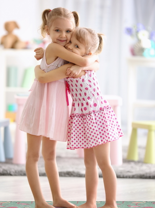 Cute little girls embracing at home